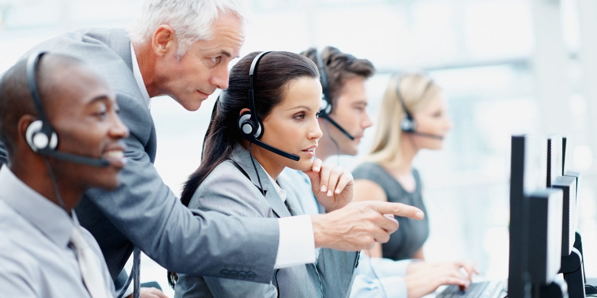 Side view of a smart senior manager and his team working in a call center